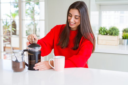 Young beautiful woman making morning coffee smiling, preparing a cup of latte for breakfast