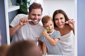 Portrait of happy family brushing teeth in the bathroom