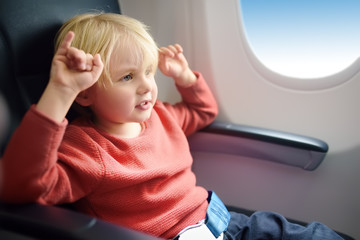 Charming kid traveling by an airplane. Little boy sitting by aircraft window during the flight. Air...