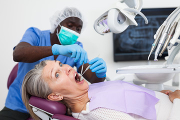 Dentist is treating female patient which is sitting in dental chair in clinic