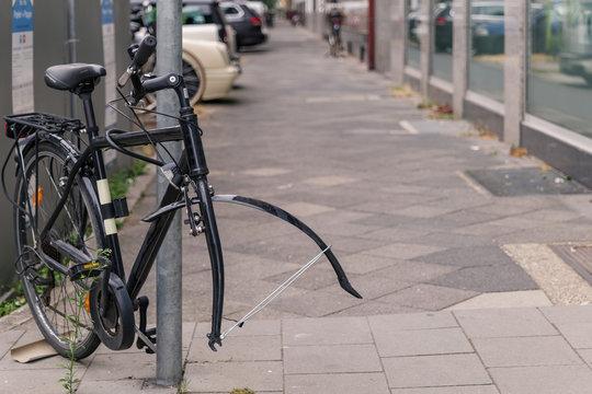 Bike or bicycle lock on steel pole on sidewalk was stolen its front wheel. Stolen wheel bicycle. Abandon vintage bicycle leave on street in Europe.
