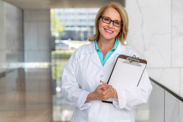 Likable warm and friendly doctor physician, healthcare professional portrait, smiling sincere with clipboard at hospital clinic