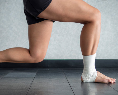 Athlete mid lunge with an ankle tape job