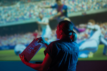 The girl is watching football, soccer in 3D, with glasses on the big screen. with popcorn, entertainment and relaxation. action, rest in the cinema. Cheerleader, fan