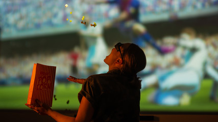 The girl is watching football, soccer in 3D,in glasses with popcorn frozen in the air, frozen in motion on a large screen.with entertainment and relaxation. action, rest in the cinema. Cheerleader,fan