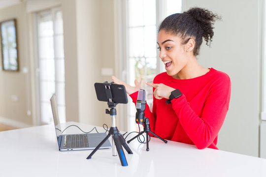 Young african american woman doing video call using smartphone camera and microphone amazed and smiling to the camera while presenting with hand and pointing with finger.