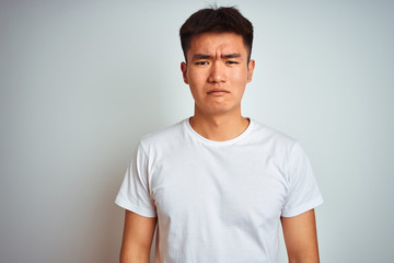 Young asian chinese man wearing t-shirt standing over isolated white background depressed and worry for distress, crying angry and afraid. Sad expression.