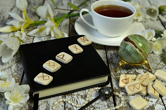 Runes on black diary book, crystal and cup of tea on witch table.