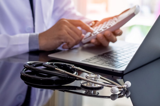 Male doctor or practitioner using calculator and working on laptop computer with medical stethoscope on the desk at clinic or hospital. Medical healthcare,fees and revenue concept.