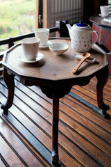 Porcelain tea set on a wooden table. Picture with grain and color from film simulation filter.