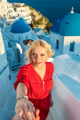 blond woman wearing a red dress, standing on stairs with her husband holding her hand and the famous blue church domes in the background