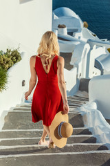blond woman in a red dress and a sun hat, walking down stairs in Oia on Santorini