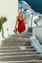 blond woman in a red dress and a sun hat, walking up stairs in Oia on Santorini