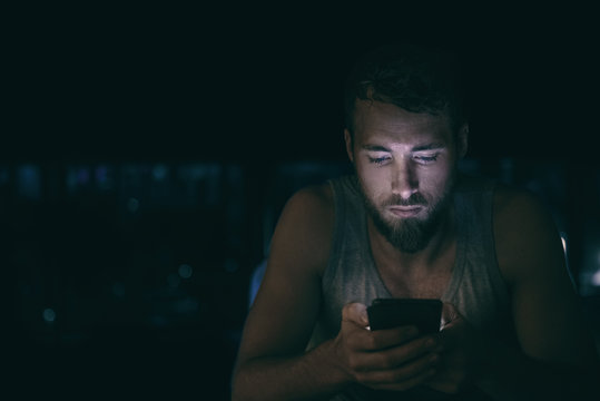 Dark night man looking at mobile phone screen texting late at night awake in bed insomnia or outside in city with skyline background. Serious looking guy depressed addicted to social media.