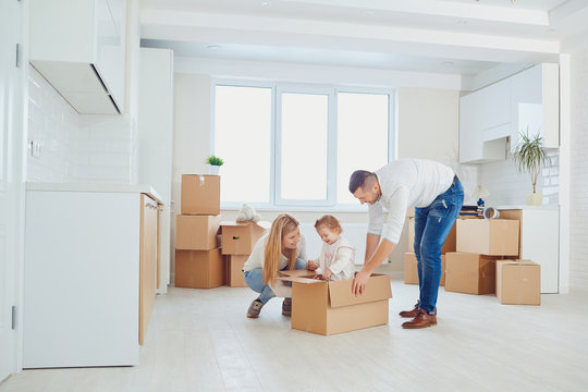 Happy family unpacking boxes at new home