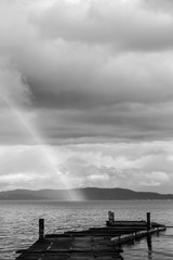 Beautiful view of a rainbow over a pier on a Trasimeno lake (Umbria, Italy)