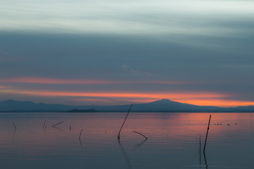 Sunset a Trasimeno lake (Umbria, Italy), with fishing net poles on the foreground