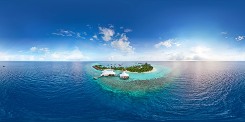 Aerial spherical panorama of tropical paradise beach  on tiny Maldives island. Turquoise ocean and white sand. Small bungalows between coconut palm trees
