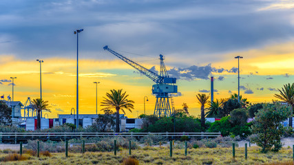 A vintage shipping crane against a yellow sunset sky
