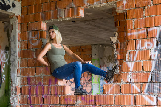CESKE BUDEJOVICE,CZECH REPUBLIC - August 19,2019 - Portrait of young woman sitting in abandoned building with graffiti