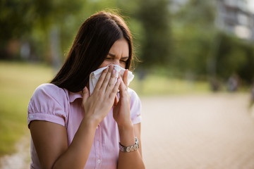 Obraz Woman with allergy symptom blowing nose in park. - fototapety do salonu