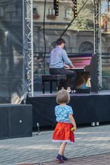 Fototapeta dziewczynka zasłuchana w muzyce spogląda na pianistę na plenerowym koncercie  obraz
