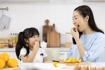 Happy Asian family Little girl eating Orange fruit and Mother are preparing the vegetables and fruit in the kitchen at home. Healthy food concept