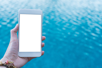Close up hand holding mobile smartphone white screen with copy space for text on blue swimming pool  background.summer displaying picture.