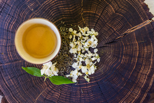 Cup of tea, green tea, dried  blossoms and sprig of jasmine on wooden board. Flat lay with space for text