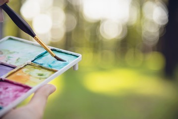 Relax woman painting water colour art work in green garden forest nature - people with creative art in nature stress reduction and meditation concept