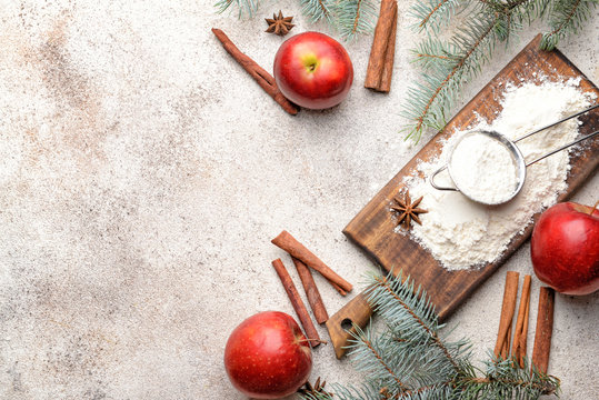 Wooden board with flour, apples and spices on grey background