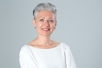 Portrait of a middle aged woman on a gray background. Wall mural