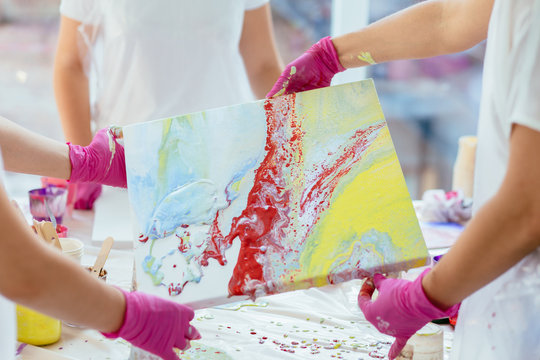Woman painter holding hair dryer while female beginnres studying creating fluid acrylic abstract painting in art therapy class, dropping paints on canvas. Close up. Study, art therapy concept.