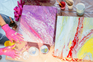 Creative woman painter teaching three female student creating fluid acrylic abstract painting in art therapy class, with table full of bottle with defferent paint colors. Art, design, creating concept