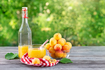 Bottle and glass of apricot juice with apricots on green background