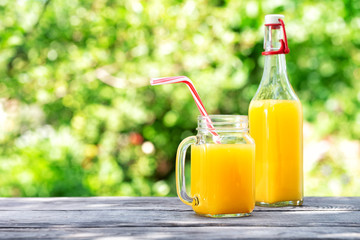 Bottle and jar with orange juice on a wooden table
