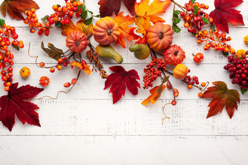 Festive autumn decor from pumpkins, berries and leaves on a white  wooden background. Concept of Thanksgiving day or Halloween. Flat lay autumn composition with copy space. Wall mural