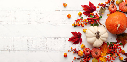 Poster Autumn Festive autumn decor from pumpkins, berries and leaves on a white wooden background. Concept of Thanksgiving day or Halloween. Flat lay autumn composition with copy space.