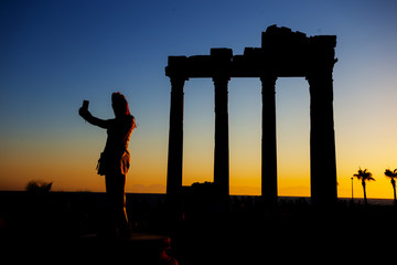Silhouette of girl making selfie on background of Temple of Apollo at sunset