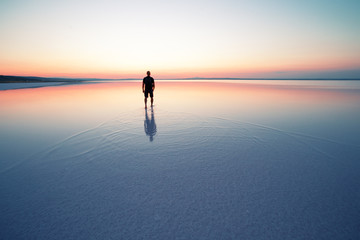 Silhouette of man departing into sunset on smooth water of lake