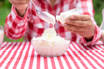 Woman puts sour cream in cottage cheese