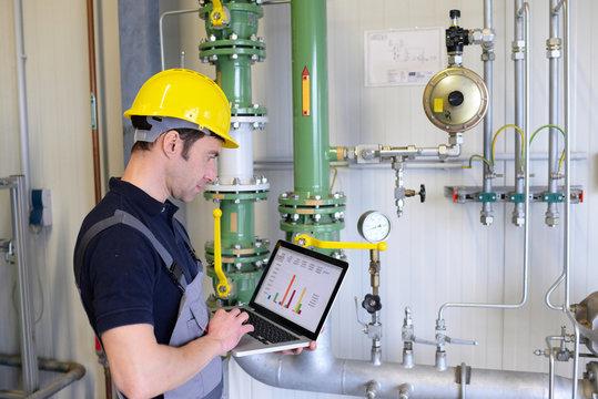 Arbeiter bei Instandhaltung einer modernen Industrieanlage - Kontrolle und Aufnahme der Daten // workers maintaining a modern industrial plant - checking and recording data