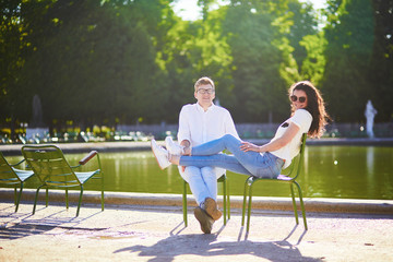 Happy romantic couple in Paris, sitting on traditional green metal chairs in Tuileries garden