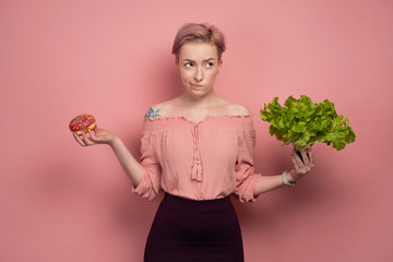 A girl with short pink hair, mockingly looking up, holding a salad and a donut in her hands, on a pink background.