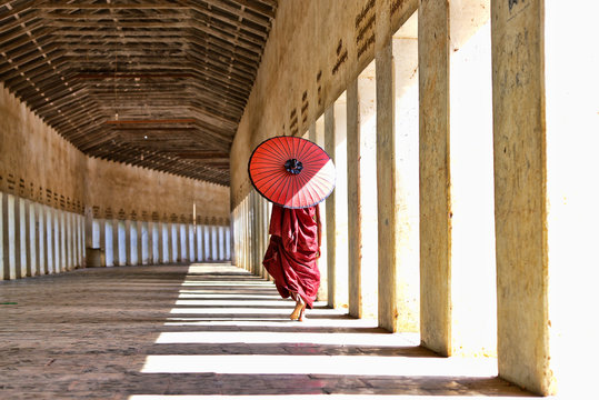 novice buddhist monks with red traditional robes holding red umbrellas walking in a white buddhist temple in myanmar