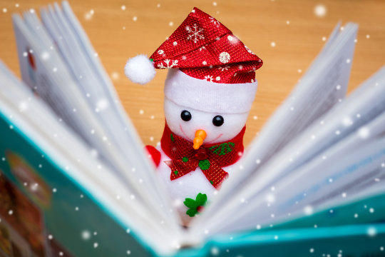 Toy snowman with open book  during snowfall. Reading your favorite books. New Year greeting card_