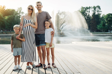 Image of young family with children on walk in park on background of fountain