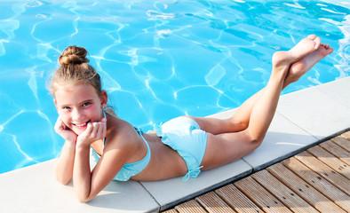Cute smiling little girl child lying near swimming pool and having fun