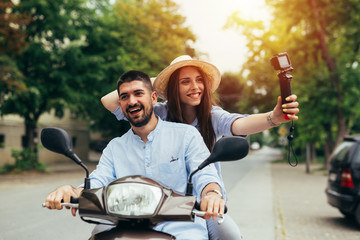 couple riding on a motorbike and taking picture with camera