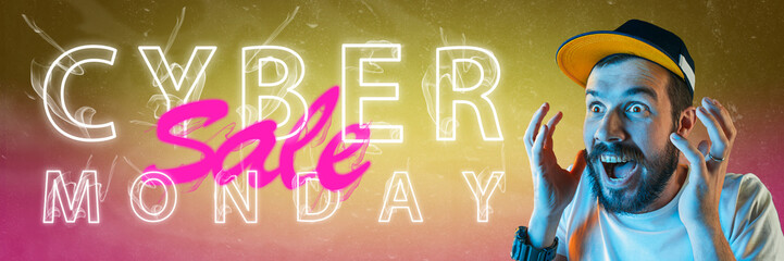Cyber monday, sales, purchases concept. Neon lighted letters on gradient background. Astonished man...